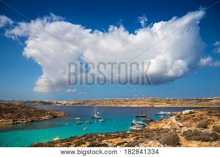 Blue Lagoon Malta - Beautiful clouds over malta's famous Blue Lagoon on the island of Comino with the island of Gozo and Mgarr town at the background on a bright sunny summer day