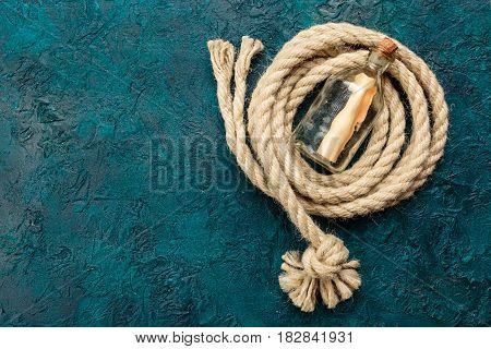 Bottle with a note and a sea rope on a dark turquoise background. Top view. Place for the text.