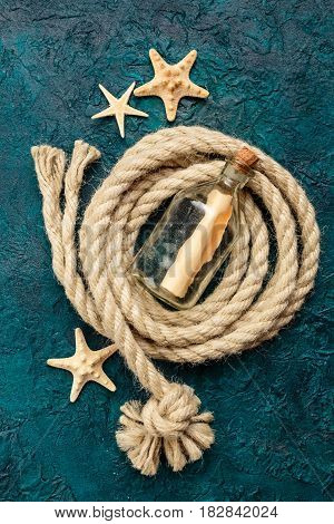 Starfish Bottle with a note and a sea rope on a dark turquoise background. Top view. Place for the text.