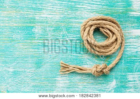 Ship rope knot on turquoise wooden background. Top view. Place for text.