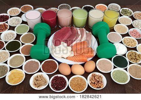 Health food and drinks for body builders with dumbbell weights on oak background.