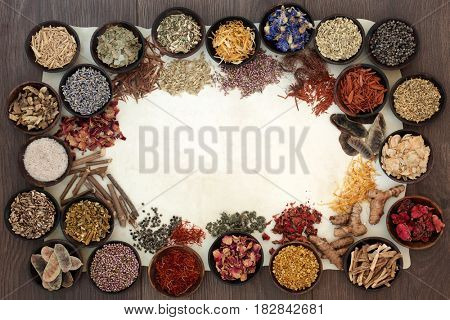 Dried medicinal herb and flower selection used in natural alternative medicine on parchment paper forming a border on oak background.