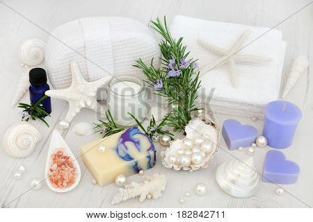 Rosemary herb flower cleansing treatment with moisturizing cream, soap, himalayan salt, aromatherapy essential oil, face towels, cloth sponge, with decorative shells and pearls.