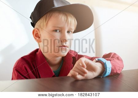 A Horoizontal Portrait Of Serious Male Child Wearing Trendy Cap And Red Shirt Having A Smart Watch O
