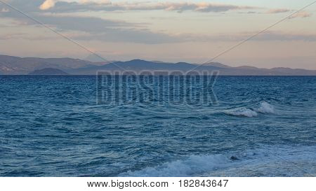 Evening storm on the blue sea overlooking the sky and mountains of the other shore Kassandra Greece