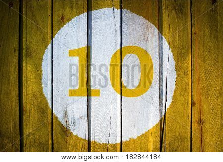 House Number Or Calendar Date In White Circle On Yellow Toned Wooden Door Background. Number Ten 10