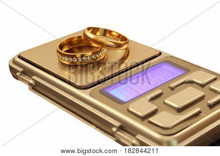 Gold wedding rings on scales isolated photo