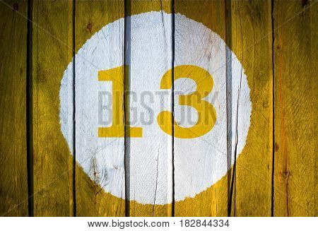 House Number Or Calendar Date In White Circle On Yellow Toned Wooden Door Background. Number Thirtee