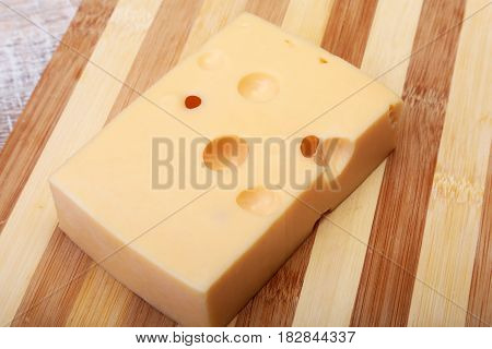 Italian piece of cheese on a wooden cutting board.