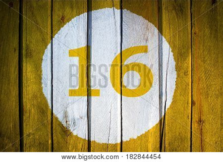 House Number Or Calendar Date In White Circle On Yellow Toned Wooden Door Background. Number Sixteen