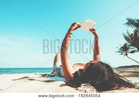 Leisure in summer - Young women lying on a tropical beach relax with book. Blue sea in the background. Summer vacation concept. vintage color tone.