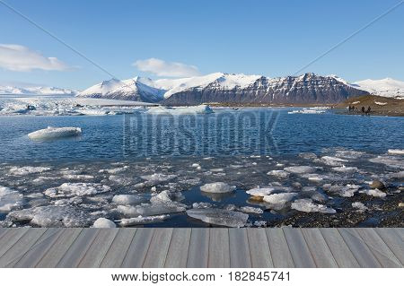 Opening wooden floor Winter natural lagoon with mountain landscape background Iceland