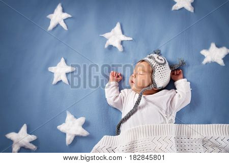 Cute newborn baby girl lying in the bed. 2 month old child in owl hat sleeping on blue blanket with stars