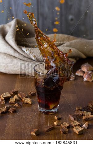 Traditional Russian drink kvass from bread rye malt sugar and water. Kvass in a glass on a dark wooden background. Splash