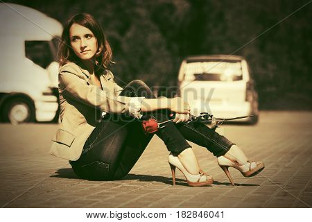 Sad young fashion woman with red rose sitting on the road