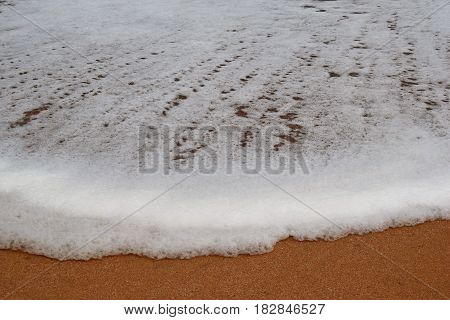 Foam and sea water enters the beach area from a broken wave at Port Alfred in the Eastern Cape of South Africa