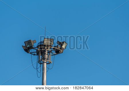 vintage tone image of sport light pole with clear blue sky.