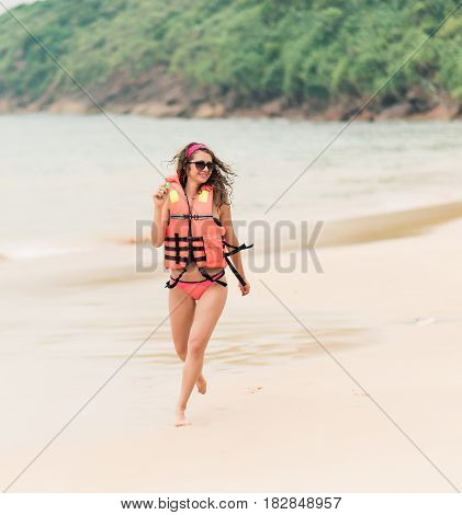 A girl in a life jacket and glasses is running along a deserted beach. A beautiful curly girl with a bright manicure in an orange life jacket monitors the safety on the beach.