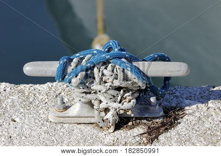 Naval ropes linked to the dock of the harbor