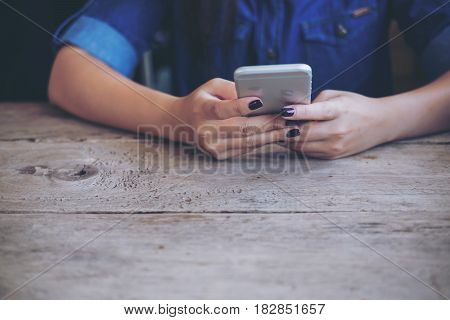 A woman holding and using smart phone on wooden table with feeling relax while sitting in vintage cafe