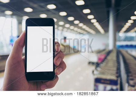 Mockup image of a man holding black mobile phone with blank white screen while standing and waiting for baggage claim in the airport