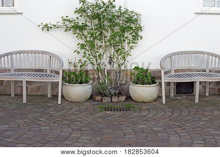 Two white benches on a house wall, silence place