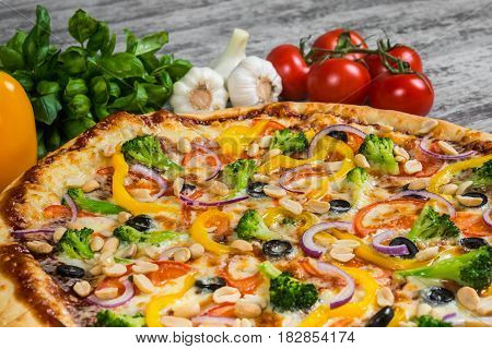 Italian pizza on a light wooden table on the background of vegetables and greens