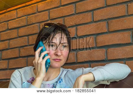 Young Brunette Woman With Short Hair Talking On Her Smartphone