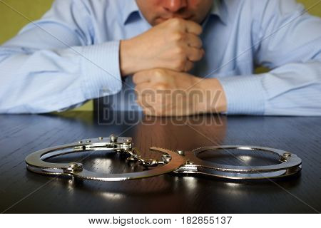 Punishment concept. Man is sitting at the table opposite handcusffs.