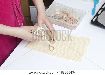 Preparation Of Meat Glomeruli. Stuffed Turkey, Wrapped In Strips Of Puff Pastry. A Woman Winds A Str