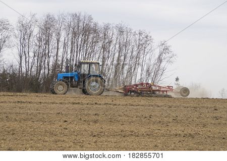 In the photo the tractor treats the soil in the spring