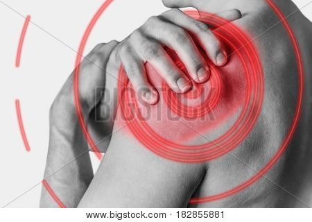 Man compresses his shoulder acute pain. Monochrome image isolated on a white background. Pain area of red color.