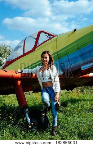 Girl on the colorful airplane parked on the grass at the airfield