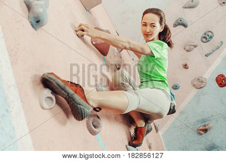 Free climber young woman training on practical wall indoor bouldering. Sportswoman smiling and looking at camera.