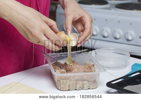 Stages Of Preparation Of Meat Glomeruli. The Woman Adds A Chicken Egg To The Stuffing. Next To The T