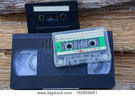 Two audio cassettes and a video cassette on wood
