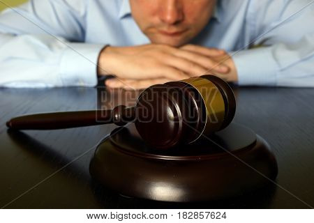 Justice concept. Man is sitting at the table opposite gavel.