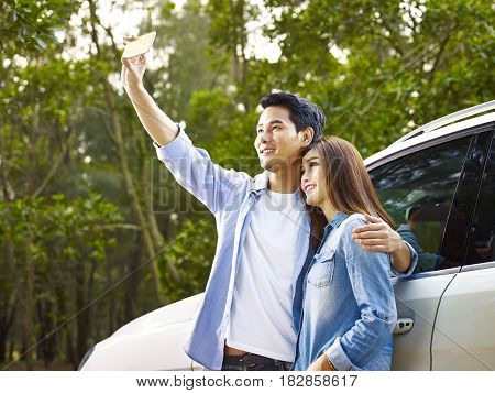 young asian couple taking a selfie during a trip.