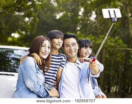 asian family with two children taking a selfie during a trip.