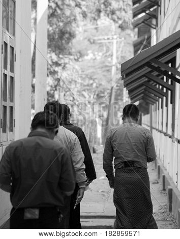 BLACK AND WHITE PHOTO OF WALKING GROUP OF PEOPLE SHOT FROM BACK