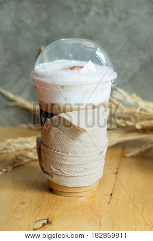 Iced latte with straw in plastic cup on wood table
