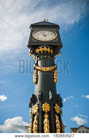 An old golden clock Tower in front of a church