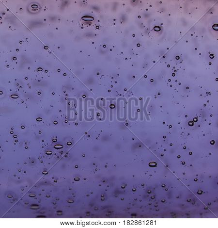 Purple blurred glass background with abstract drops