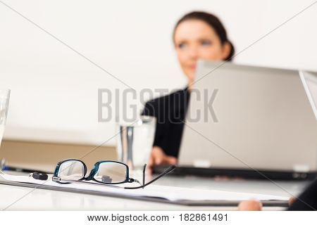 business woman sitting in conference room. focus on glasses in the foreground.