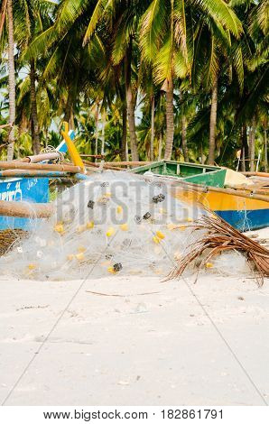 White fishing net on coral sand beach with colorful boats and palms in background
