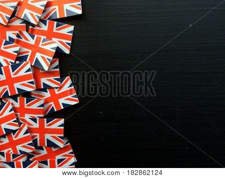 Paper Union Jack flags of the United Kingdom at the edge of a blackboard with copy space provided for words and text