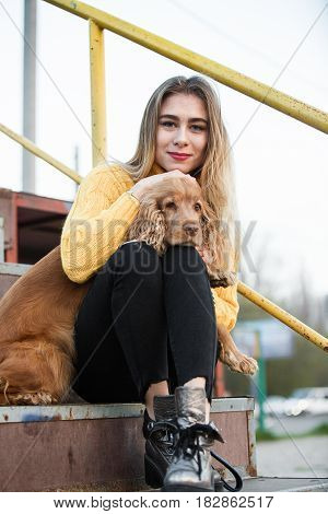 Portrait. A beautiful sexy girl, blonde, a young woman, looking like Jennifer Aniston sitting with a Cocker Spaniel dog, on a rusty metal stairway. Smiling