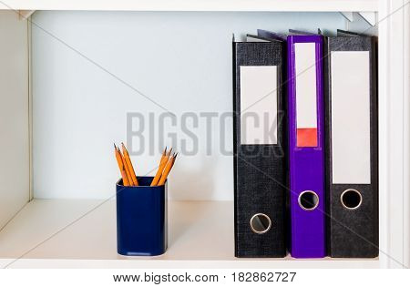 White shelf with office folders and pencil holder