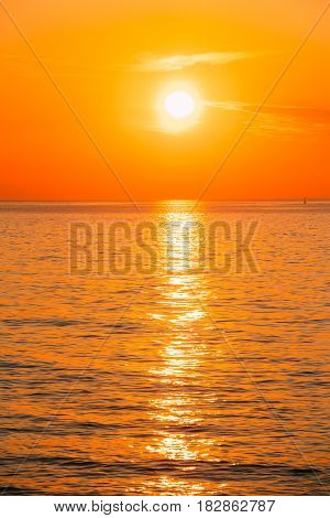 Sun Is Setting On Horizon At Sunset Sunrise Over Sea Or Ocean. Tranquil Sea Ocean Waves. Natural Sky Warm Colors.