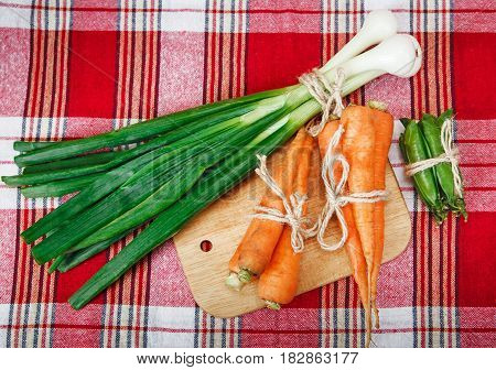 Green fresh onion and orange carrot with twine on the check red tablecloth and wooden board.Vegetables.